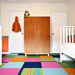 Réalisation d'une chambre d'enfant de 1 à 3 ans design avec moquette, un sol multicolore et un mur orange.