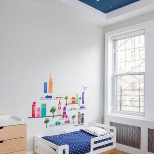 Foto di una cameretta da bambino da 1 a 3 anni contemporanea con pareti bianche e pavimento in legno massello medio