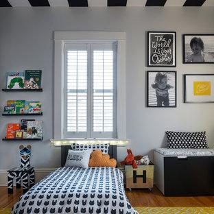 Imagen de dormitorio infantil de 1 a 3 años, clásico renovado, pequeño, con paredes grises, suelo de madera en tonos medios y suelo marrón