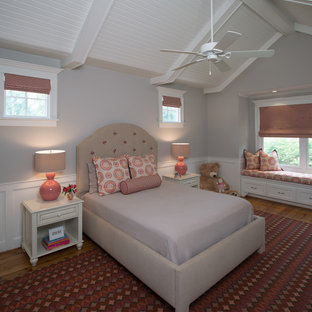 Example of a large classic girl medium tone wood floor kids' room design in Houston with gray walls