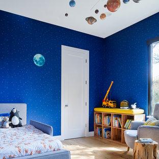 Inspiration pour une chambre d'enfant de 1 à 3 ans design avec un mur bleu, un sol en bois clair et un sol beige.