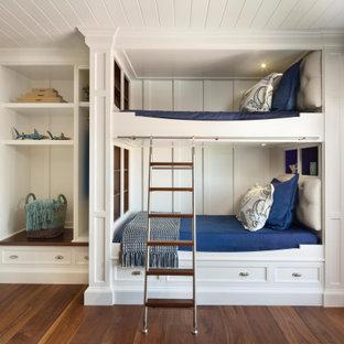Esempio di una cameretta per bambini da 4 a 10 anni costiera di medie dimensioni con pavimento in legno massello medio, pavimento marrone, pareti bianche e soffitto in perlinato