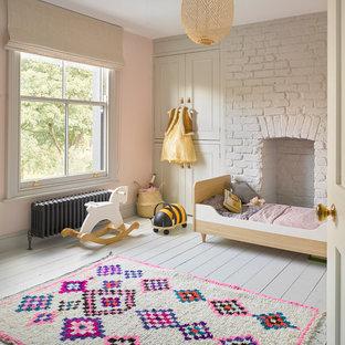 Skandinavisches Kinderzimmer mit Schlafplatz, rosa Wandfarbe, gebeiztem Holzboden und weißem Boden in London