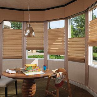 Esempio di una cameretta per bambini da 1 a 3 anni moderna di medie dimensioni con pareti beige e pavimento in ardesia