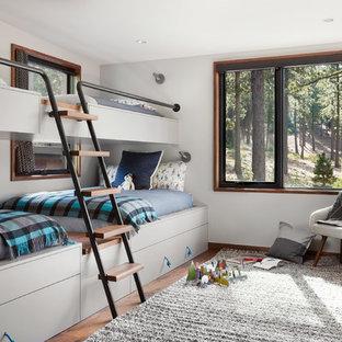 Idee per una grande cameretta per bambini design con pareti bianche, pavimento marrone e pavimento in legno massello medio