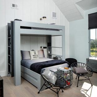 Lantlig inredning av ett stort barnrum kombinerat med sovrum, med vita väggar, mellanmörkt trägolv och grått golv