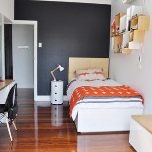 Exempel på ett mellanstort modernt barnrum kombinerat med sovrum, med mellanmörkt trägolv och svarta väggar