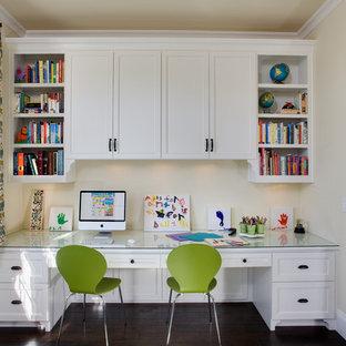 Réalisation d'une grand chambre neutre de 4 à 10 ans tradition avec un bureau, un mur jaune et un sol en bois foncé.