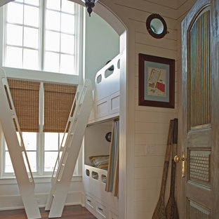 Beach style gender neutral toddler's room in Miami with white walls and dark hardwood flooring.