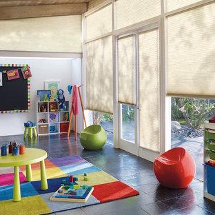 Esempio di una grande cameretta per bambini da 1 a 3 anni bohémian con pareti bianche e pavimento in ardesia