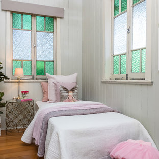 This is an example of a country kids' bedroom for girls in Brisbane with grey walls, medium hardwood floors and brown floor.