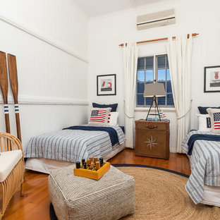 Beach style kids' bedroom in Brisbane with white walls, medium hardwood floors and brown floor for kids 4-10 years old and boys.