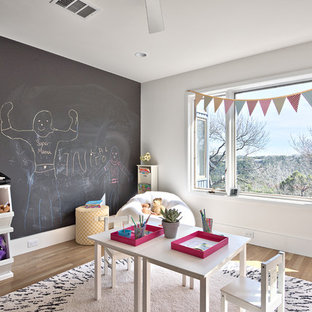 Example of a danish gender-neutral light wood floor and beige floor kids' room design in Austin with white walls