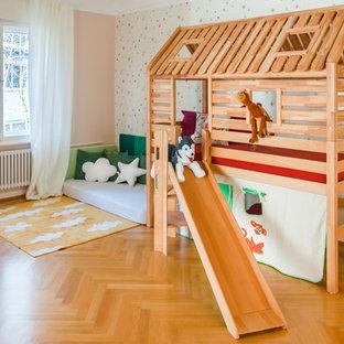 Ispirazione per una cameretta per bambini da 1 a 3 anni nordica di medie dimensioni con pavimento in legno massello medio, pavimento marrone e pareti multicolore