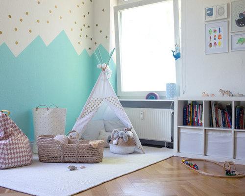 Mittelgroßes, Neutrales Skandinavisches Kinderzimmer Mit Weißer Wandfarbe,  Braunem Holzboden, Beigem Boden Und Spielecke