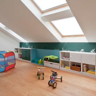 Modern inredning av ett mycket stort könsneutralt barnrum kombinerat med lekrum och för 4-10-åringar, med mellanmörkt trägolv och flerfärgade väggar