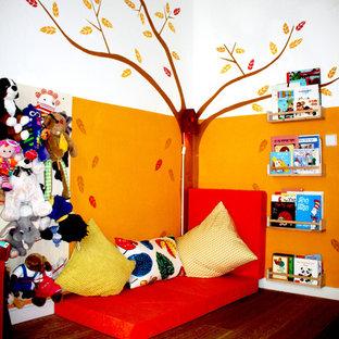 Inredning av ett modernt mellanstort könsneutralt småbarnsrum kombinerat med lekrum, med flerfärgade väggar, laminatgolv och brunt golv