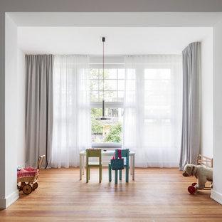 Neutrales, Großes Modernes Kinderzimmer mit Spielecke, weißer Wandfarbe und braunem Holzboden in Köln