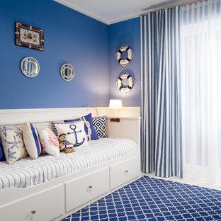 Inredning av ett maritimt mellanstort pojkrum kombinerat med sovrum och för 4-10-åringar, med blå väggar, klinkergolv i porslin och vitt golv