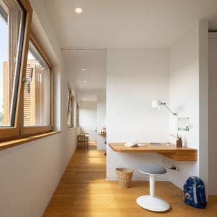 Foto di una cameretta per bambini minimal di medie dimensioni con pareti bianche, pavimento in legno massello medio e pavimento marrone