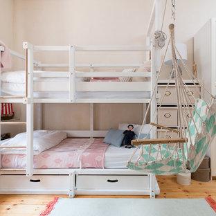 Kleines Maritimes Kinderzimmer mit Schlafplatz, rosa Wandfarbe, braunem Holzboden und braunem Boden in Berlin