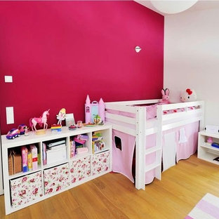 Modern inredning av ett stort flickrum kombinerat med sovrum och för 4-10-åringar, med vita väggar, ljust trägolv och brunt golv