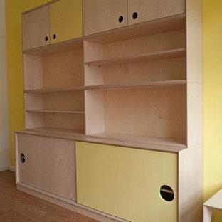 Idée de décoration pour une chambre d'enfant de 4 à 10 ans design de taille moyenne avec un mur jaune et un sol en bambou.
