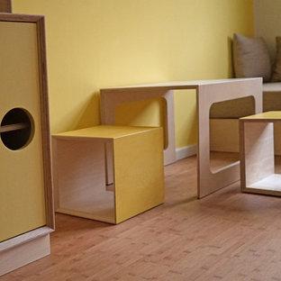 Exempel på ett mellanstort modernt flickrum kombinerat med lekrum och för 4-10-åringar, med gula väggar och bambugolv