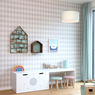 Mittelgroßes, Neutrales Skandinavisches Kinderzimmer mit Spielecke, weißer Wandfarbe, braunem Holzboden und beigem Boden in Hamburg