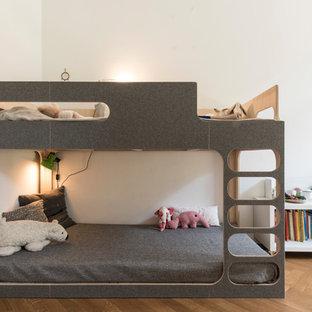 Immagine di una grande cameretta per bambini da 4 a 10 anni moderna con pareti bianche e parquet chiaro