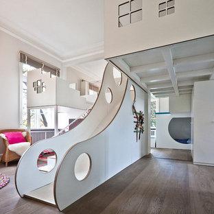 Idee per un'ampia cameretta per bambini da 4 a 10 anni design con pareti bianche e pavimento in legno massello medio