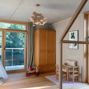 Skandinavisches Kinderzimmer mit Spielecke, beiger Wandfarbe, braunem Holzboden und braunem Boden in München
