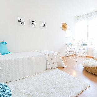 Bild på ett mellanstort maritimt barnrum kombinerat med sovrum, med vita väggar, laminatgolv och brunt golv
