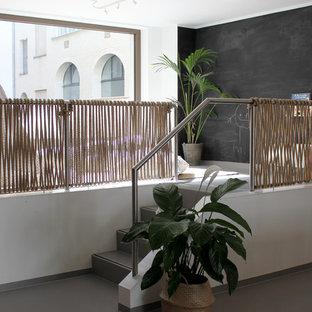 Exempel på ett mellanstort modernt könsneutralt barnrum kombinerat med lekrum och för 4-10-åringar, med vita väggar, grått golv och betonggolv