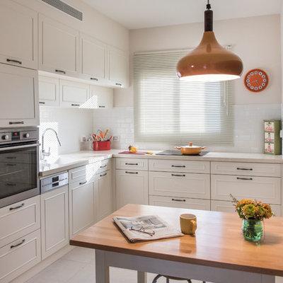 Elegant l-shaped kitchen photo in Tel Aviv with white cabinets, white backsplash, subway tile backsplash, stainless steel appliances and an island