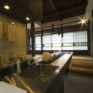 Mid-sized asian open concept kitchen ideas - Example of a mid-sized zen single-wall slate floor open concept kitchen design in Yokohama with an undermount sink, dark wood cabinets, stainless steel countertops, black appliances, an island and beige countertops