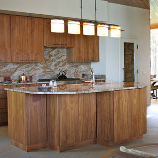 Photo of a mid-sized midcentury l-shaped open plan kitchen in Other with an undermount sink, flat-panel cabinets, medium wood cabinets, granite benchtops, brown splashback, stone slab splashback, stainless steel appliances, ceramic floors, with island, beige floor and brown benchtop.