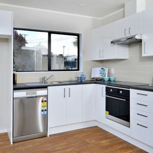 Design ideas for a small beach style l-shaped eat-in kitchen in Auckland with a single-bowl sink, flat-panel cabinets, white cabinets, laminate benchtops, ceramic splashback, stainless steel appliances, vinyl floors and no island.