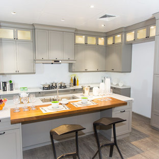 Design ideas for a large rustic l-shaped kitchen/diner in Melbourne with a submerged sink, shaker cabinets, engineered stone countertops, black appliances, grey cabinets, plywood flooring, an island, brown floors and white worktops.
