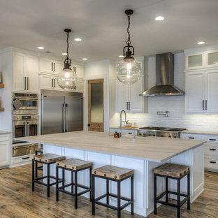 Lantlig inredning av ett grå grått l-kök, med en rustik diskho, skåp i shakerstil, vita skåp, vitt stänkskydd, stänkskydd i tegel, rostfria vitvaror, mörkt trägolv, en köksö och brunt golv