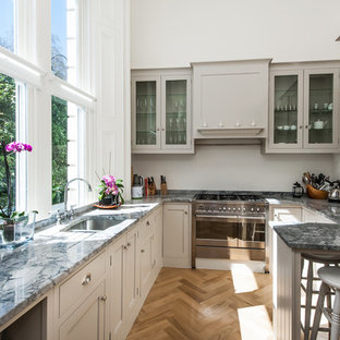 Inspiration for a medium sized classic u-shaped kitchen in Surrey with a submerged sink, shaker cabinets, grey cabinets, granite worktops, grey splashback, stainless steel appliances, medium hardwood flooring and a breakfast bar.