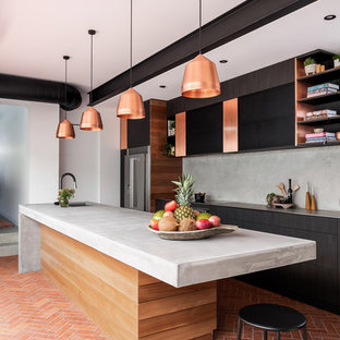 Photo of a large industrial galley separate kitchen in Perth with an undermount sink, flat-panel cabinets, dark wood cabinets, concrete benchtops, grey splashback, stainless steel appliances, brick floors, with island, red floor and grey benchtop.