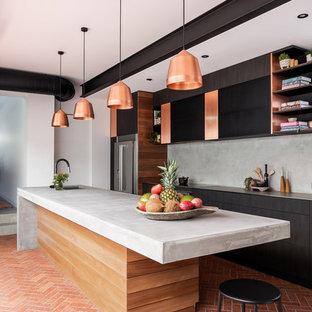 Идея дизайна: большая отдельная, параллельная кухня в стиле лофт с врезной раковиной, плоскими фасадами, темными деревянными фасадами, столешницей из бетона, серым фартуком, техникой из нержавеющей стали, кирпичным полом, островом, красным полом и серой столешницей