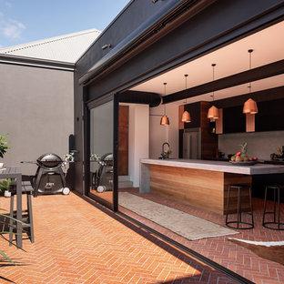 Immagine di una grande cucina parallela industriale chiusa con lavello sottopiano, ante lisce, ante in legno bruno, top in cemento, paraspruzzi grigio, elettrodomestici in acciaio inossidabile, pavimento in mattoni, isola, pavimento rosso e top grigio