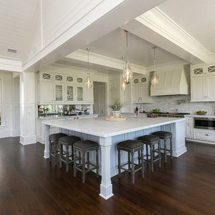 Transitional eat-in kitchen inspiration - Example of a transitional dark wood floor eat-in kitchen design in Charleston with beaded inset cabinets, white cabinets, gray backsplash, stainless steel appliances and an island