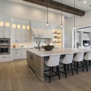 オレンジカウンティのトランジショナルスタイルのおしゃれなキッチン (シェーカースタイル扉のキャビネット、白いキャビネット、白いキッチンパネル、シルバーの調理設備、無垢フローリング、茶色い床、白いキッチンカウンター) の写真