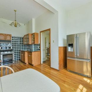 ボストンの大きいトラディショナルスタイルのおしゃれなキッチン (ドロップインシンク、レイズドパネル扉のキャビネット、中間色木目調キャビネット、人工大理石カウンター、黒いキッチンパネル、セラミックタイルのキッチンパネル、シルバーの調理設備の、淡色無垢フローリング、アイランドなし、ベージュの床、緑のキッチンカウンター) の写真