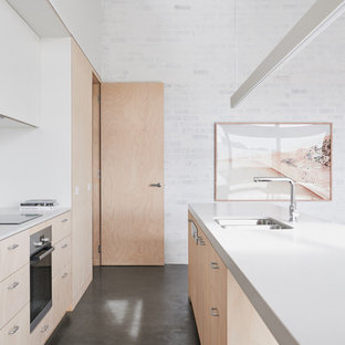 Inspiration for a contemporary galley open plan kitchen in Melbourne with a double-bowl sink, flat-panel cabinets, light wood cabinets, stainless steel appliances, concrete floors, with island, white splashback, ceramic splashback and grey floor.