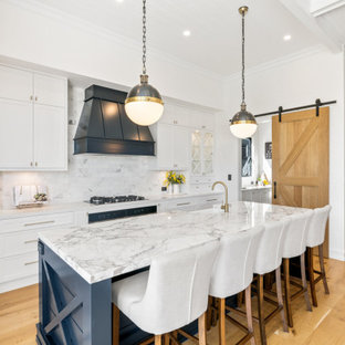 This is an example of a country galley kitchen in Brisbane with a farmhouse sink, shaker cabinets, white cabinets, white splashback, stainless steel appliances, medium hardwood floors, with island, brown floor and white benchtop.