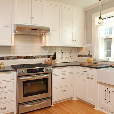 Inspiration for a small craftsman u-shaped light wood floor enclosed kitchen remodel in Minneapolis with a farmhouse sink, white cabinets, multicolored backsplash, stainless steel appliances, recessed-panel cabinets, subway tile backsplash, no island and soapstone countertops